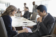 Businessman and businesswoman using digital tablet in conference room meeting - HEROF29246