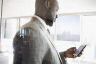 Businessman texting with cell phone - HEROF29252