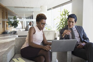 Businessman and businesswoman using laptop in office lounge - HEROF29255