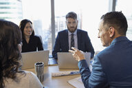 Business people with laptops talking in conference room meeting - HEROF29297
