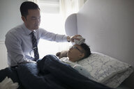 Businessman father placing cold washcloth on forehead of son laying in bed with fever - HEROF29333