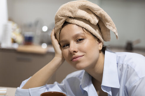Portrait of smiling young woman with with hair wrapped in a towel in the kitchen - VGF00227