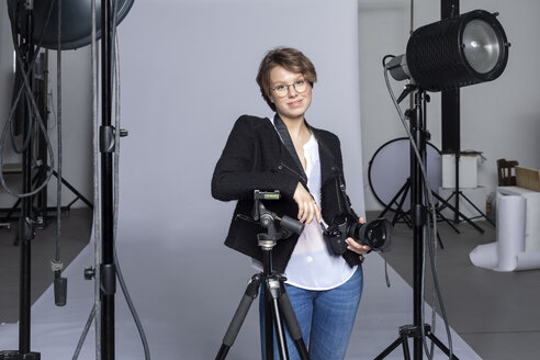 Portrait of smiling young photographer with equipment at photographic studio - VGF00239