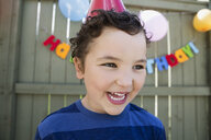 Close up enthusiastic boy wearing birthday party hat - HEROF29349