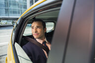 Businessman looking out window of taxi - HEROF29385