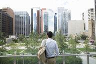 Businessman looking at city view - HEROF29403
