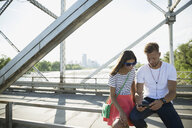Couple texting with cell phone on sunny bridge - HEROF29427