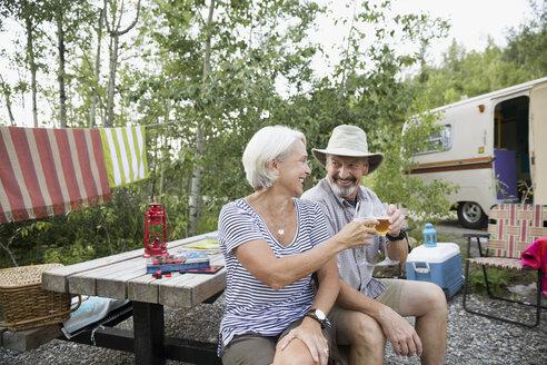Senior couple toasting wine glasses campsite picnic table - HEROF29454
