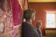Senior woman drinking coffee at tapestry - HEROF29463