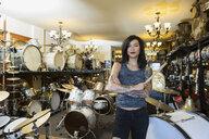 Portrait confident music shop owner holding drumsticks - HEROF29550