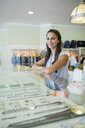 Portrait confident worker at jewelry display case shop - HEROF29574