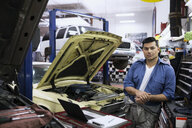 Portrait serious mechanic in auto repair shop - HEROF29580