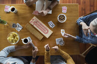 Overhead view of young friends playing cribbage table - HEROF29616