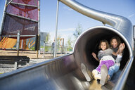 Mother and daughter sliding out tunnel slide playground - HEROF29643