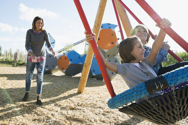 Mother pushing daughter and son in playground swing - HEROF29646