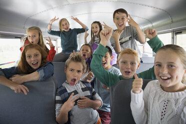Portrait confident school kids gesturing on school bus - HEROF29652