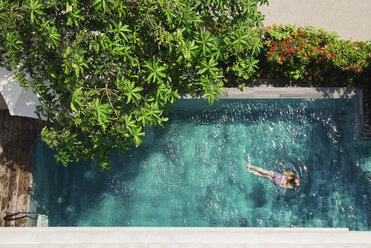High angle view of girl swimming in pool during sunny day - CAVF63159