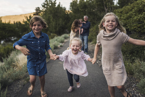 Happy sisters holding hands while running on road against parents in forest - CAVF63186