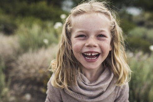 Portrait of happy girl with blond hair standing against plants in forest - CAVF63204