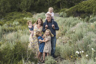 Portrait of happy parents with cute daughters standing on field amidst plants in forest - CAVF63207