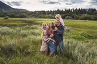 Portrait of happy parents with cute daughters standing on grassy field against sky in forest - CAVF63210
