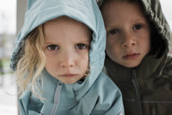 Close-up portrait of siblings in raincoats standing at home - CAVF63225