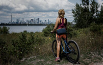 Rear view of woman with bicycle looking at river against modern buildings during sunny day - CAVF63228