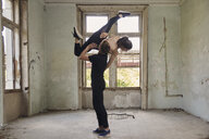 Man lifting ballerina while dancing in old building - CAVF63255