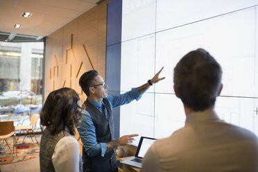 Architects discussing blueprints on projection screen conference room - HEROF29669