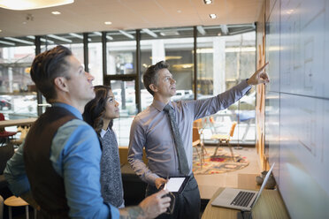 Architects discussing blueprints on projection screen conference room - HEROF29672