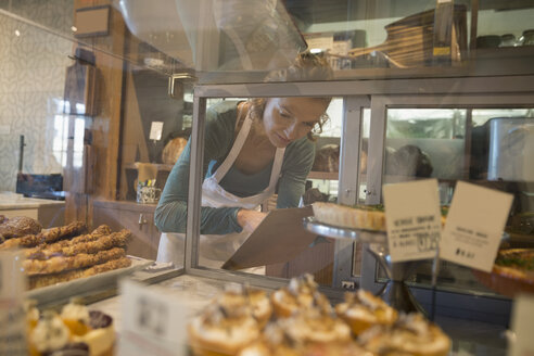 Bakery owner with clipboard checking inventory - HEROF29696