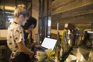 Baristas using laptop in coffee shop - HEROF29714