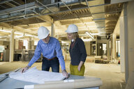 Architect and engineer reviewing blueprints office construction site - HEROF29771