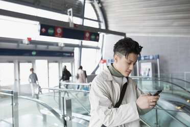 Young man texting with cell phone train station - HEROF29793