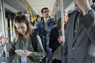Young woman texting cell phone standing on bus - HEROF29829