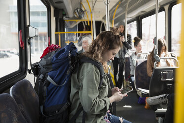 Young woman backpack texting cell phone on bus - HEROF29832