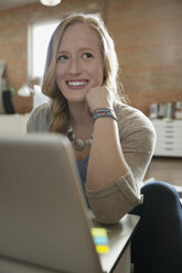 Smiling female designer using laptop looking away - HEROF29880