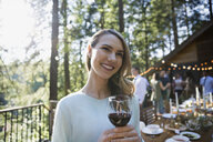 Smiling woman drinking red wine at wedding reception - HEROF29895