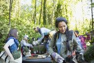 Tree planting volunteers preparing at truck bed in woods - HEROF29919