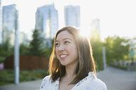 Smiling woman looking away on city street - HEROF29955