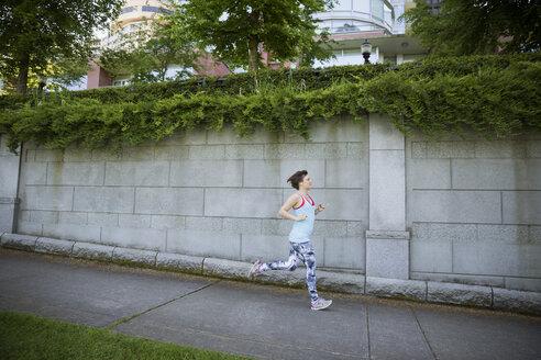 Woman running on suburban sidewalk - HEROF29958