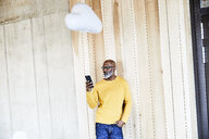 Mature businessman holding cell phone attached to cloud balloon - FMKF05444