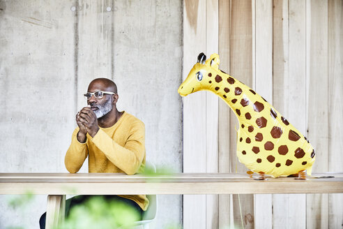 Mature businessman sitting at desk in office next to giraffe figurine - FMKF05453