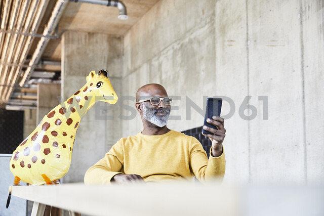 Smiling mature businessman sitting at desk in office with cell phone and giraffe figurine - FMKF05456