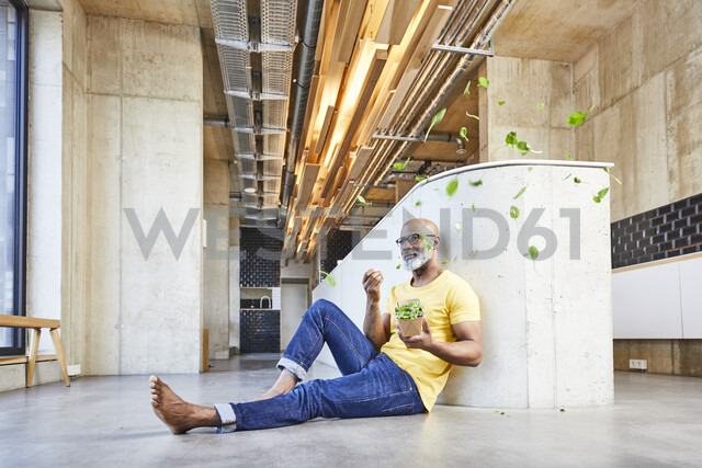 Mature businessman sitting on the floor in modern office surrounded by floating lettuce leaves - FMKF05468