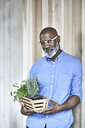 Portrait of confident mature businessman holding plants in office - FMKF05489