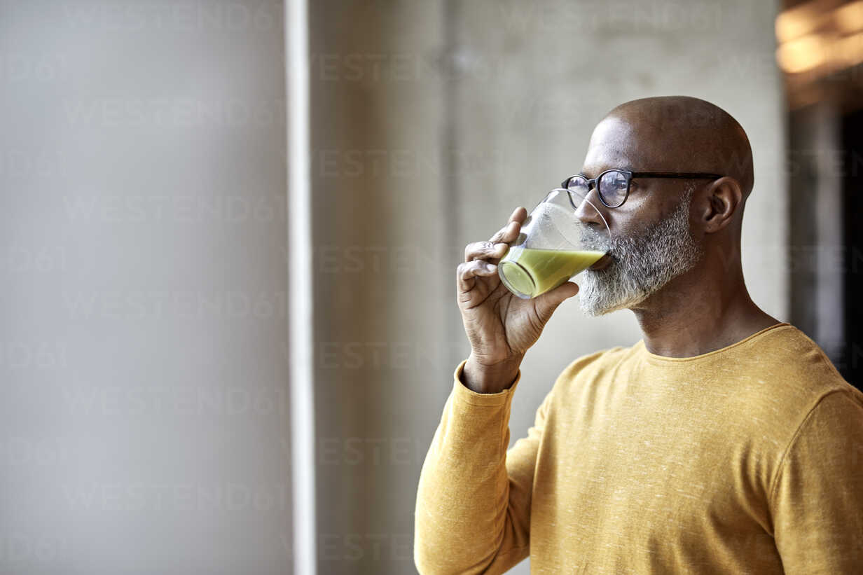 Mature businessman in office drinking a smoothie - FMKF05501 - Jo Kirchherr/Westend61