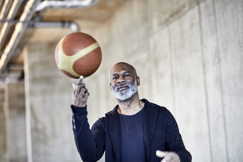 Portrait of mature businessman with basketball in modern office - FMKF05504