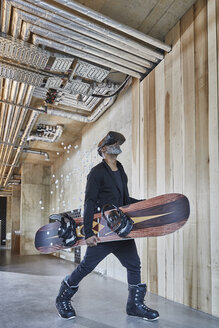 Mature businessman wearing VR glasses holding snowboard in modern office - FMKF05510