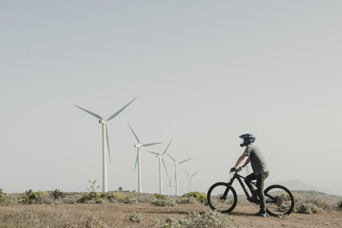 Spain, Lanzarote, mountainbiker on a trip in desertic landscape with wind turbines in background - AHSF00078